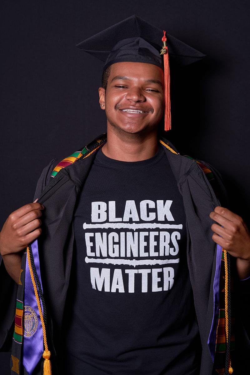 Christopher in graduation cap and gown while revealing a t-shirt underneath that says Black Engineers Matter