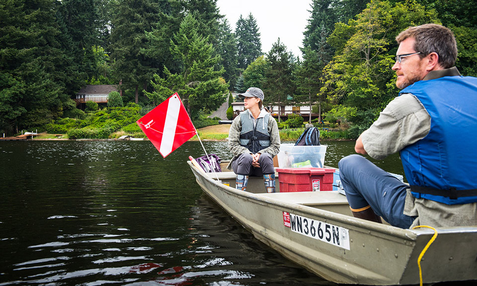 Graduate student Samantha Fung sitting in a boat with professor Alex Horner-Devine on a lake