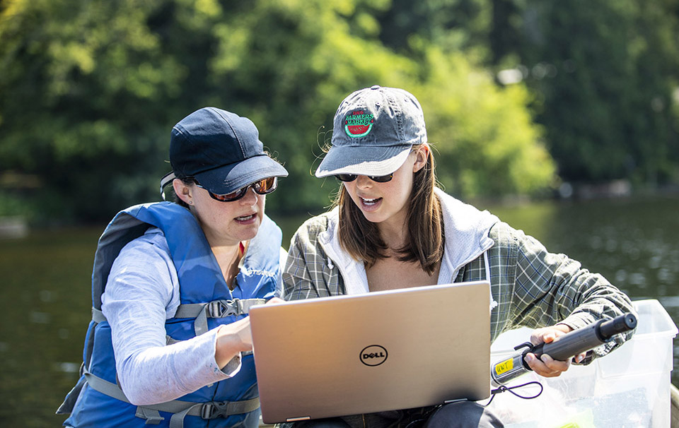 Associate professor Rebecca Neumann and graduate student Samantha Fung looking at a laptop screen together