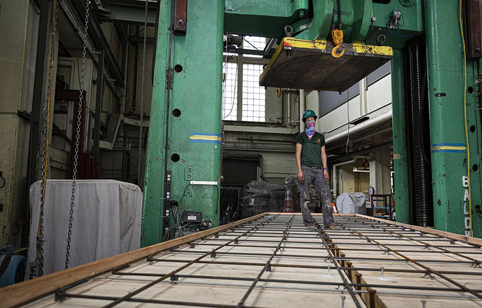 KPFF structural design engineer Addie Lederman stands on the composite beam specimen underneath the Big Baldwin platen