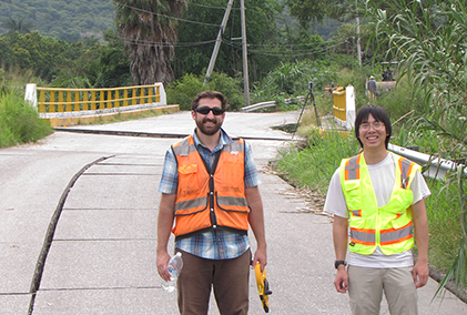 Jake Dafni and Eric Lo stand in front of a damaged roadway