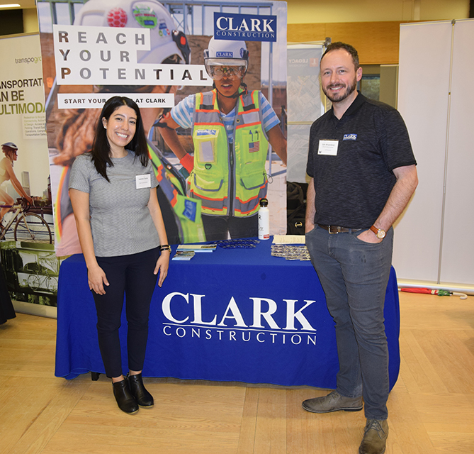 Clark Construction employers standing in front of their booth