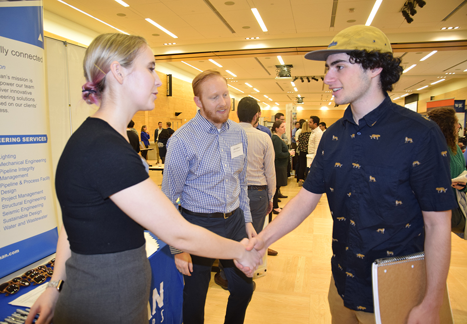 An employer shaking a student's hand
