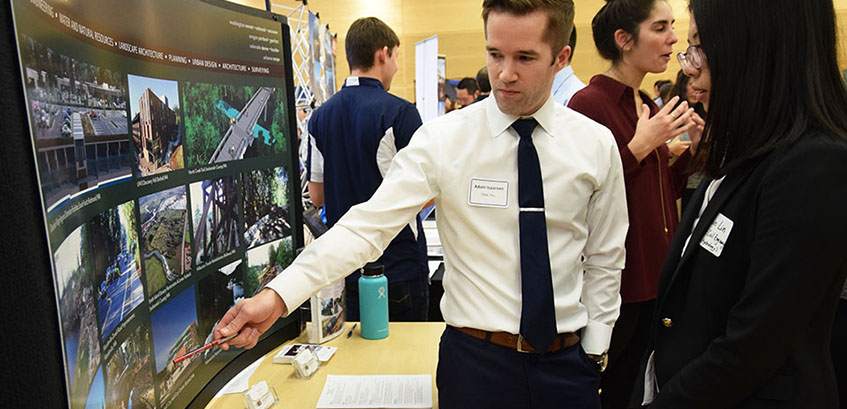 person explaining career fair display to student