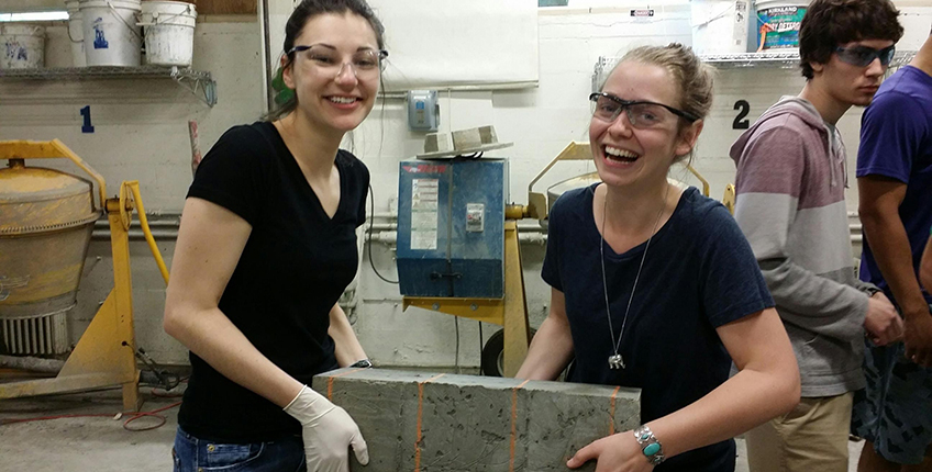 two students holding concrete