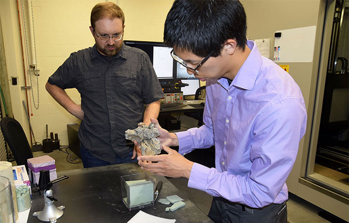 Randall Irmis watches as CEE ​lab manager Sean Yeung prepares a marine crocodilian skull to be scanned