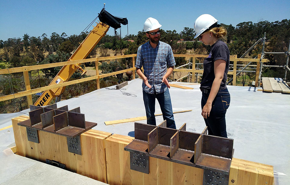 Standing on top of the roof of the two-story structure, associate professor Jeff Berman and graduate student Sarah Wichman discuss the installation process for the walls, the PT bars, and the connections. Photo Credit: Shiling Pei.