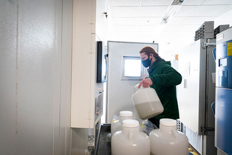 Researcher carrying jugs of wastewater sample for storing in a lab