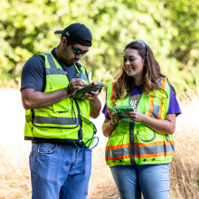 Two students wearing yellow safety vests out doing research in the field